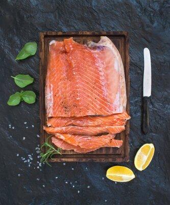 Nálepka Uzený losos filet s citronem, čerstvých bylinek a chováni na dřevěné servírovací desce přes tmavé kamenné pozadí
