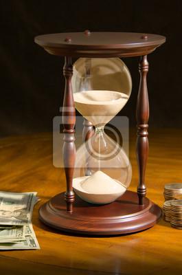 Velký přesýpací hodiny obklopen papírovým hotovosti peněz a mince na dřevěný stůl reprezentující čas běží ven, investování času, termíny, stres, finanční plánování a moudrost, která přichází s časem.