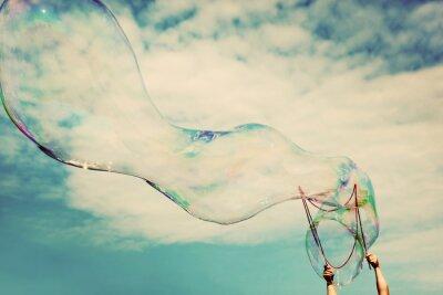 Nálepka Vyfukování velkých mýdlových bublin ve vzduchu. Vintage svoboda, letní koncepty.