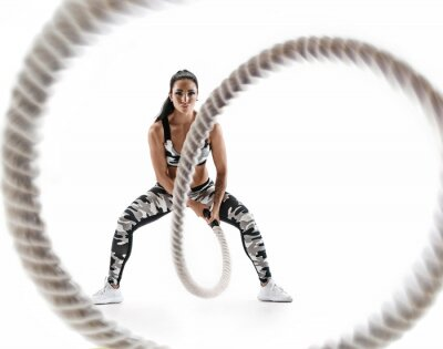Nálepka Woman doing exercises with battle rope. Photo of muscular model in military sportswear isolated on white background. Strength and motivation
