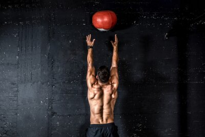 Nálepka Young strong sweaty focused fit muscular man with big muscles doing throwing medicine ball up on the wall for training hard core workout in the gym real people selective focus