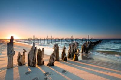 Nálepka Západ slunce na pláži Baltského moře a staré dřevěné vlnolam