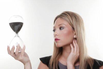 žena drží velký skleněný písku časovač v ruce sledování času dojdou