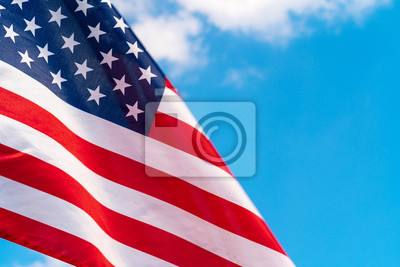 Obraz American flag waving in the wind against blue sky