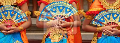 Obraz Asijské cestovní pozadí. Skupina krásných balijských tanečnic v tradičních sarongských kostýmech s fanoušky v rukou tančících Legong dance. Umění, kultura indonéského lidu, festivaly na ostrově Bali.
