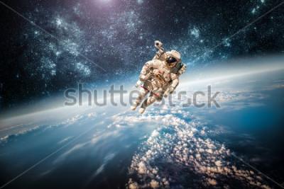 Obraz Astronaut ve vesmíru na pozadí planety Země. První obrázek tohoto NASA.