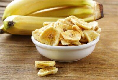 Obraz banánové chipsy, sušené ovoce na dřevěný stůl