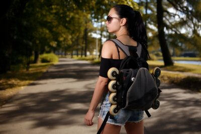 Obraz Beautiful girl brunette with backpack behind back in which roller skates
