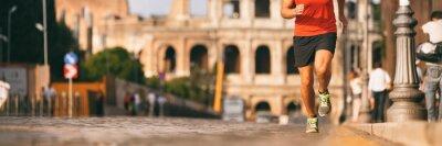 Obraz Běžec běží v římské ulici na maratónském běhu. Banner panorama sportovce nohy a běžecké boty ve venkovním pozadí.