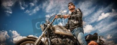 Obraz Biker muž na sobě kožené bundy a sluneční brýle sedí na jeho motocyklu.