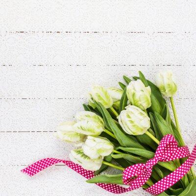 Obraz Bílé tulipány zdobený červenou stužku na bílém ubruse. Kopie vesmíru, pohled shora