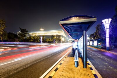 Obraz bus station next to a road at night
