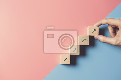 Obraz Business concept growth success process, Close up man hand arranging wood block stacking as step stair on paper blue and pink background, copy space.