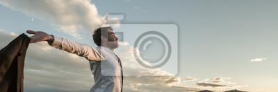 Obraz Businessman embracing life standing under cloudy sky