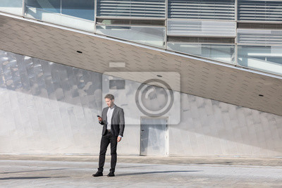 Obraz Businessman using mobile phone app texting outside of office in urban modern city building background. Young caucasian man holding smartphone for business work.