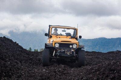 Obraz Čelní pohled na kudrnaté vlasy řidič v yelow offroad vozidla zaparkované v horní části údolí s vulkanickou skále a hory na bali, indonésie