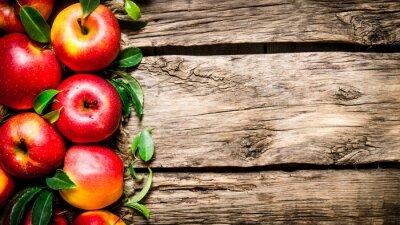 Obraz Čerstvá červená jablka se zelenými listy na dřevěném stole.