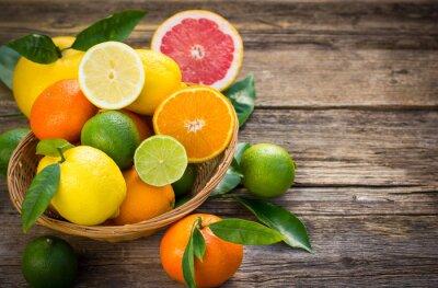 Obraz Čerstvé a šťavnaté citrusové plody v koši na rustikální stůl
