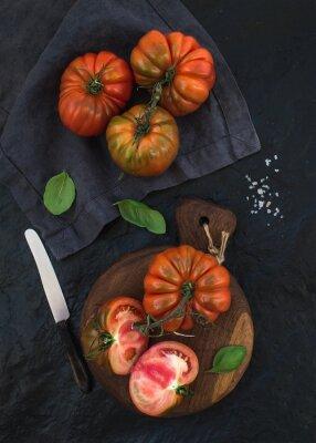 Obraz Čerstvé zralé hairloom rajčaty a bazalkou listy na rustikální dřevěné desce na černém pozadí kamene.
