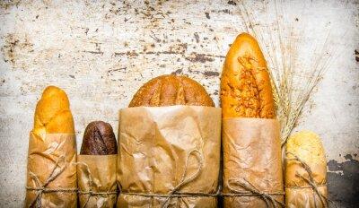 Obraz Čerstvý chléb zabalené v papíru. Na rustikální pozadí.