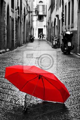 Červená deštník na dlážděné ulici ve starém městě. Vítr a déšť