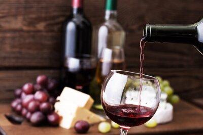 Obraz Červené víno nalil do sklenice, close-up.