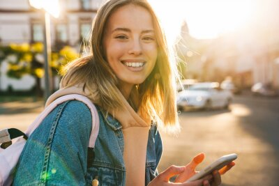 Obraz Cheerful young blonde girl using mobile phone