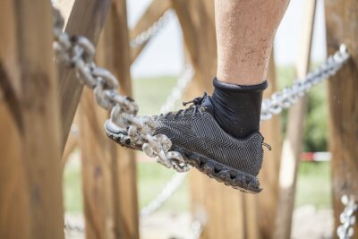 Obraz Close up of an athlete's feet wearing sports shoes on a challenging dirt track. Trail running workout on rocky terrain outdoors.