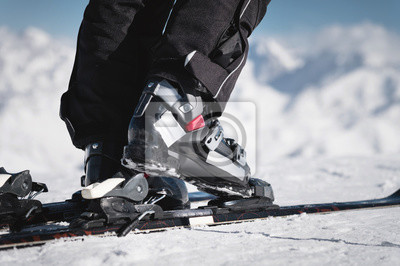 Obraz Close-up of the athlete's skier's foot in ski boots rises into the skis against the background of the snow-capped Caucasus mountains on a sunny day. Winter sports concept