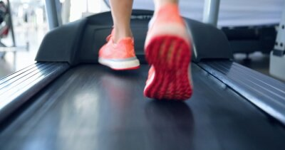 Obraz Close up on athlete's feet working out in gym. Doing cardio training on treadmill. Running on treadmill.