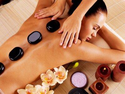Obraz Dospělá žena má masáž horkými kameny v lázeňském salonu