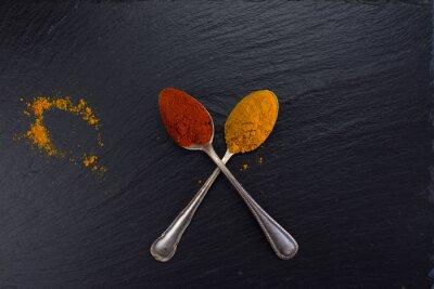 Obraz Dva vinobraní lžíce s kořením kari a papriky na černém pozadí.