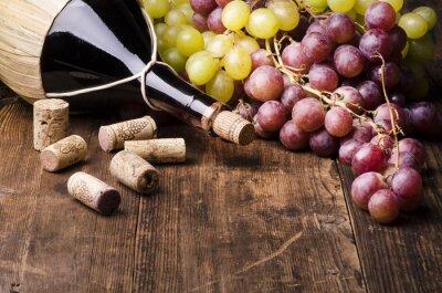 Obraz fiasko di vino con uva e turaccioli su Tavola di Legno