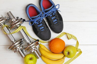 Obraz fitness equipment and healthy nutrition on white wooden plank fl