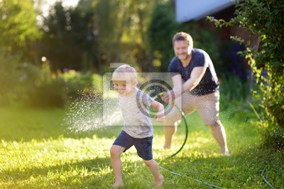 Obraz Funny little boy with his father playing with garden hose in sunny backyard. Preschooler child having fun with spray of water.