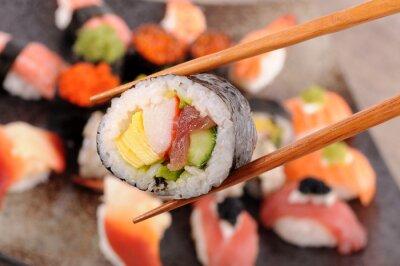 Obraz Futomaki sushi držení hůlky
