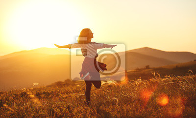 Obraz Happy woman jumping and enjoying life  at sunset in mountains.