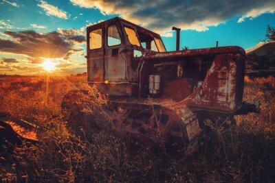 Obraz HDR obraz starého hrdzavého traktoru v poli. Západ slunce
