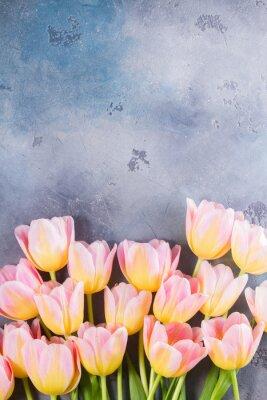 Obraz Hranice růžové a žluté tulipány na šedém kamenném pozadí s kopií prostoru