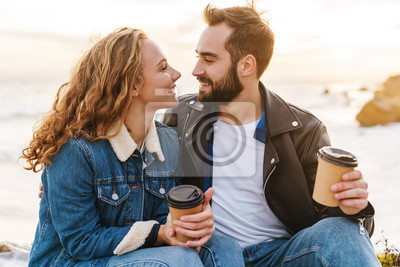 Obraz Image of beautiful young couple drinking coffee while walking by seaside
