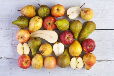 Obraz jablka a hrušky celé a poloviční zastřelil shora na bílé dřevěné desky
