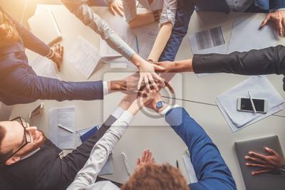 Obraz Koncepce jednoty. Close-up lidí drží ruce dohromady, zatímco sedí kolem stolu