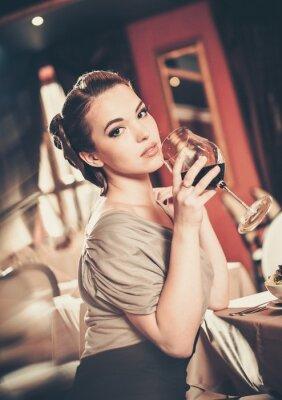 Obraz Krásná mladá dívka se sklenicí červeného winein restaurace