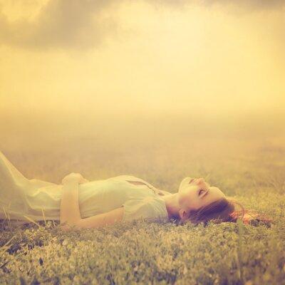 Obraz Krásná mladá dívka sní o tom, ležící na kouzelném louce na jaře