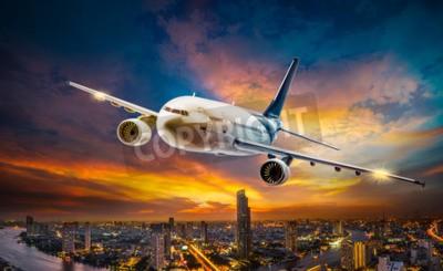 Obraz Letadlo pro přepravu létání přes město noční scény na krásné pozadí západu slunce