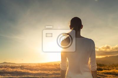 Obraz Life is beautiful. Woman standing facing a beautiful golden sunrise.