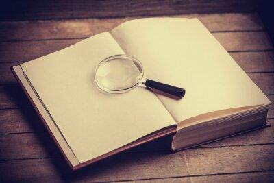 Obraz Loupa a knihy o dřevěný stůl