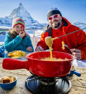 Obraz Lyžaři v restauraci, fondue, tradiční švýcarské jídlo - Matterhorn ve švýcarských Alpách v pozadí