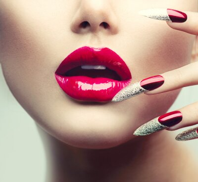 Obraz Make-up a manikúru. Červené dlouhé nehty a červené lesklé rty