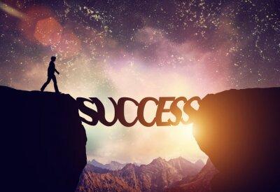 Obraz Man about to walk over precipice on SUCCESS word bridge